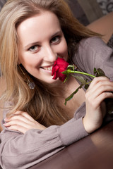 Sensual blonde girl with a red rose