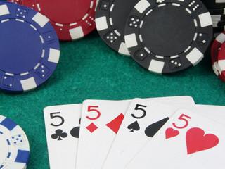 Cincos sobre un tapete verde con fichas de apostar