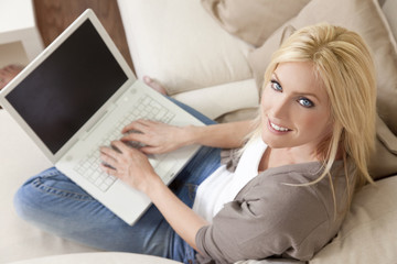 Young Woman Using Laptop Computer At Home on Sofa