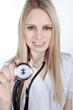Junge freundliche blonde Ärztin mit Stetoskop