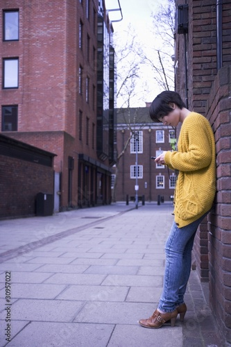 A young female adult using her phone while leaning on the wall