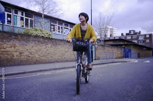 A young female adult riding her bicycle