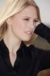 Blonde junge Frau hört zu, hoch