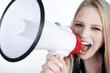 Blonde junge Frau mit Megafon fordert auf,quer
