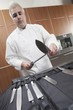 Mid- adult chef sharpens knife