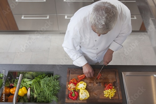Mid- adult chef dices peppers, overview