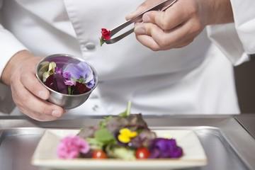 Mid- adult chef arranges edible flowers on salad