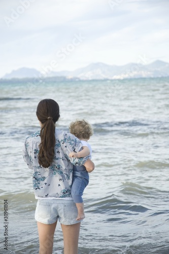 A lady holding a toddler standing in front of the sea with mountains in the far background