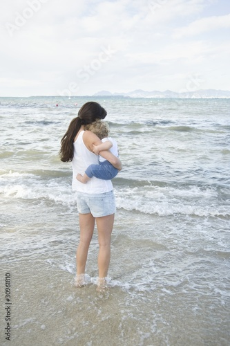 A lady holding a toddler with her feet in the shallow water, standing in front of the sea with mountains in the far background