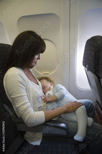 Mother and toddler on an aeroplane with the window blind down. The toddler is asleep cuddling a toy rabbit, while the mother looks at them