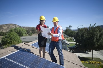Two business people on a rooftop next to solar panelling, holding up a set of plans