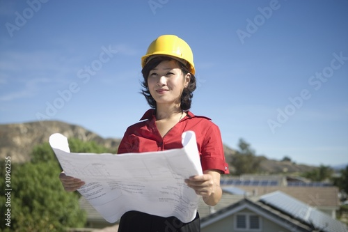 A business lady on a rooftop with plans in her hand