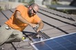 One man working on solar panelling on a roof top