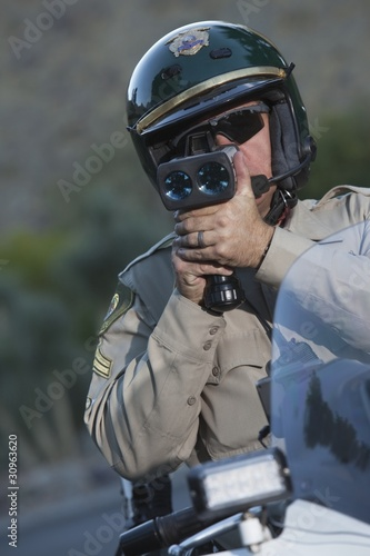 Traffic policeman sits on motorcycle looking through pseedometer