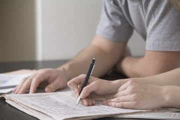 Young woman writes in newspaper with ballpoint pen