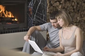 Young couple sit with laptop beside open fire