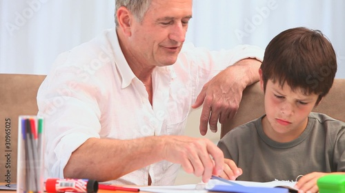 A grandfather helping his grandson to do his homeworks