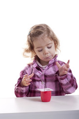 little girl licking her fingers full of yogurt