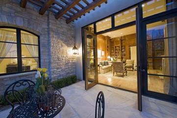 House exterior at night with some patio furniture and open patio doors looking into the lit interior