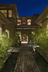 House exterior at night with wooden walkway over water