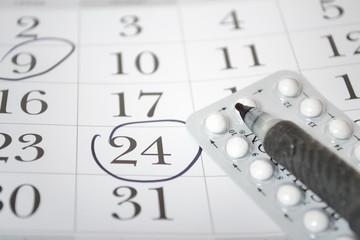 Birth control pills and pen closeup