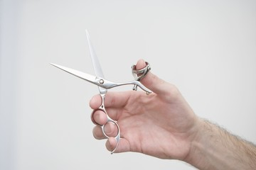 A mans hand holding scissors