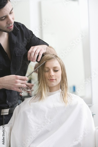 Man cutting a young womans hair in the hairdressers
