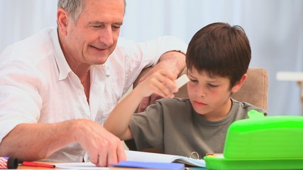 Cute little boy colouring with his grandfather