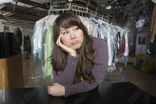 Woman working in the laundrette looking bored