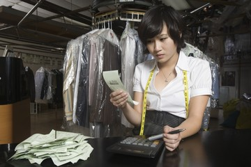 Woman working in the laundrette calculating receipts