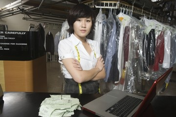 Woman standing infront of a laptop, working in a laundrette