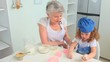 Cute curly-haired girl baking with her grandmother