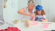 Grandmother teaching to her grand daughter how to bake