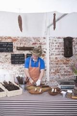 Mature man prepares speciality sausages