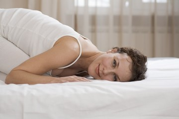 Mid adult woman kneels on bed smiling at camera
