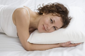 Mid adult woman lies on pillow smiling at camera
