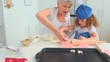 Grandmother an dher grand daughter cooking together