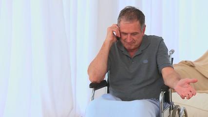 A male in a wheelchair having a phone call