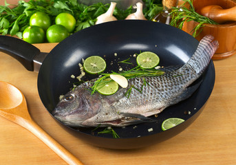 Raw tilapia with condiments in frying pan