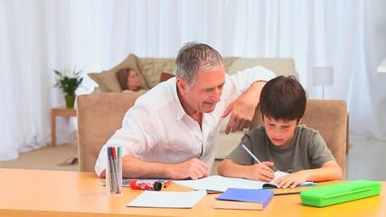 Little dark-haired boy doing homeworks