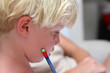 Young blonde boy doing homework with pencil