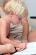 Young blonde boy doing homework with pencil and his mother helpi
