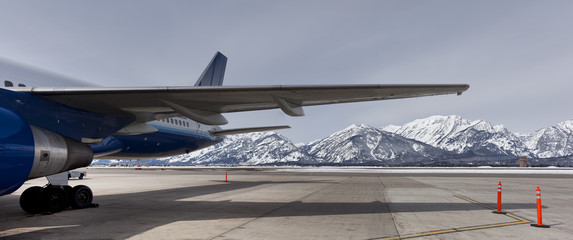 View of the teton range under an airplane wing