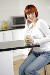 Young female enjoying a hot drink in her kitchen