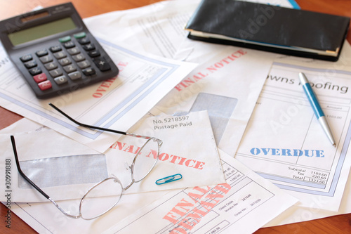 """Overdue Unpaid Bills on Table with Calculator and Cheque Book"