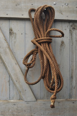 Three-strand twisted natural fibre rope on wooden door