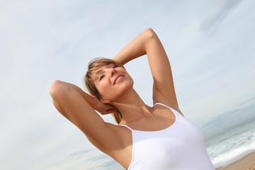 Beautiful woman breathing fresh air at the beach