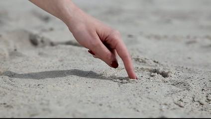 Female hand make circle over sand.