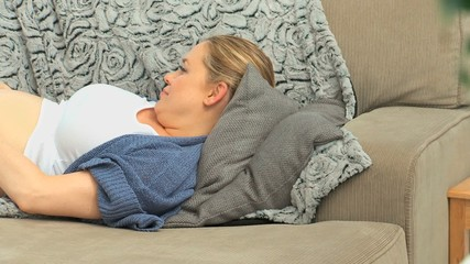 Pregnant woman laying on her couch