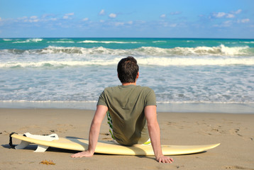 Surfer Sitting on his board and Watching the Waves